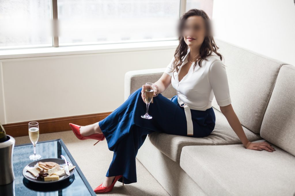 Miss Jordan Quinn wearing a white and blue jumpsuit with red heels, sitting on a couch, holding a glass of wine