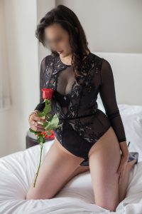 Miss Jordan Quinn wearing a black body suit and holding a red rose