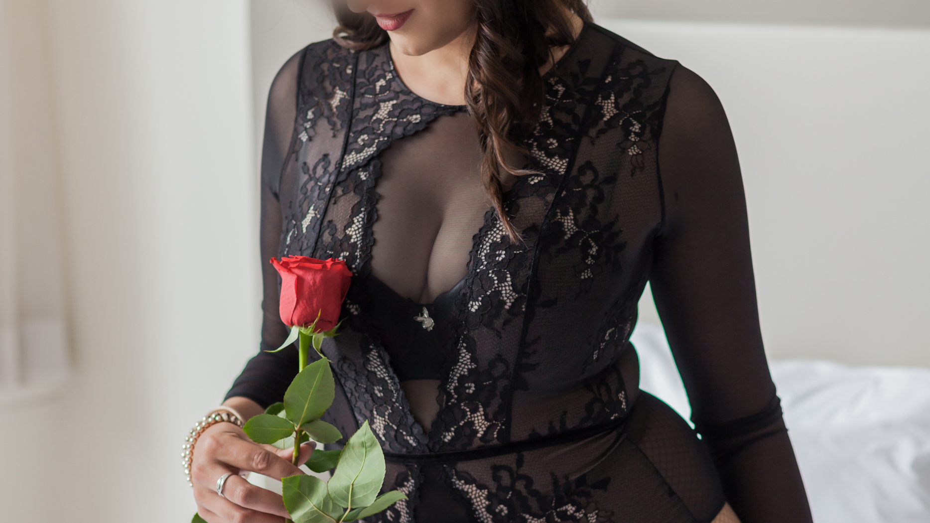 Miss Jordan Quinn, Torso shot, wearing a neck high black lace one piece, she is looking down at a red rose.