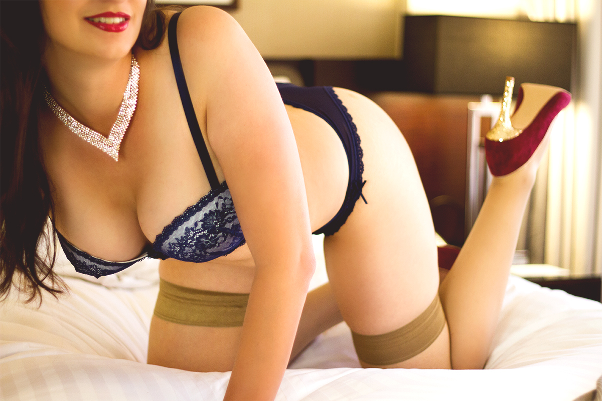 Miss Jordan Quinn posed on all fours on the bed, wearing blue lingerie and a sparkly gold and diamond necklace