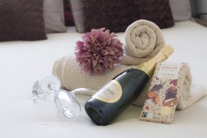 On a bed, is arranged two cream rolled towels, a bottle of champagne, two flutes, a flower and a block of chocolate