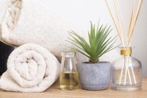 Two cream towels rolled neatly, next to a bottle filled with oil, a fake plant and a scent diffuser.l